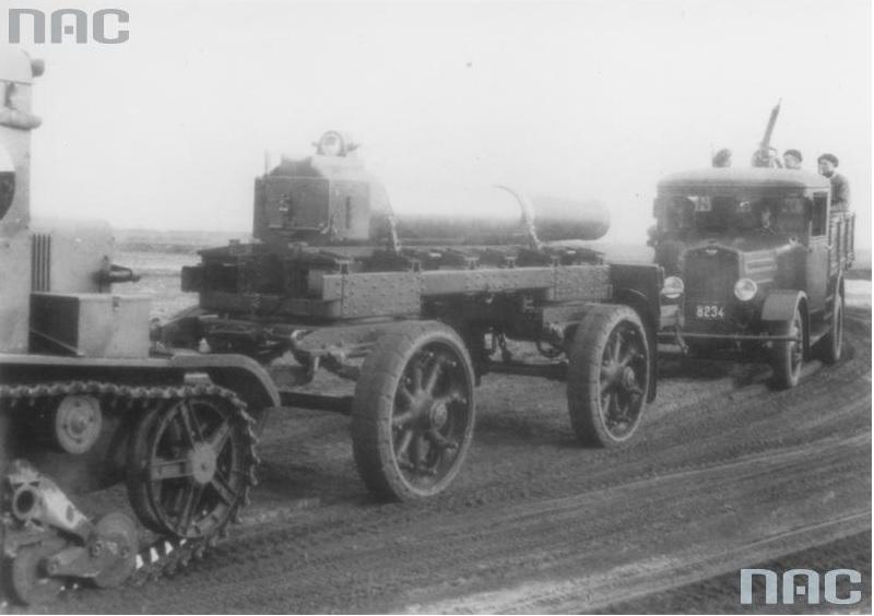 Ciągnik artyleryjski C7P z przyczepą do przewozu lufy moździerza 220 mm wz. 32 w marszu. Za ciągnikiem widoczny samochód ciężarowy Ursus A